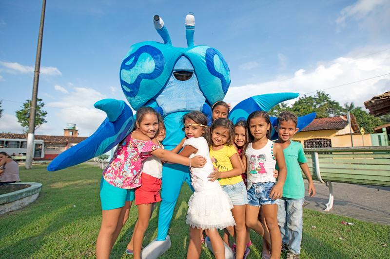 Local kids with a crab mascot during a campaign launch event in Caeté.