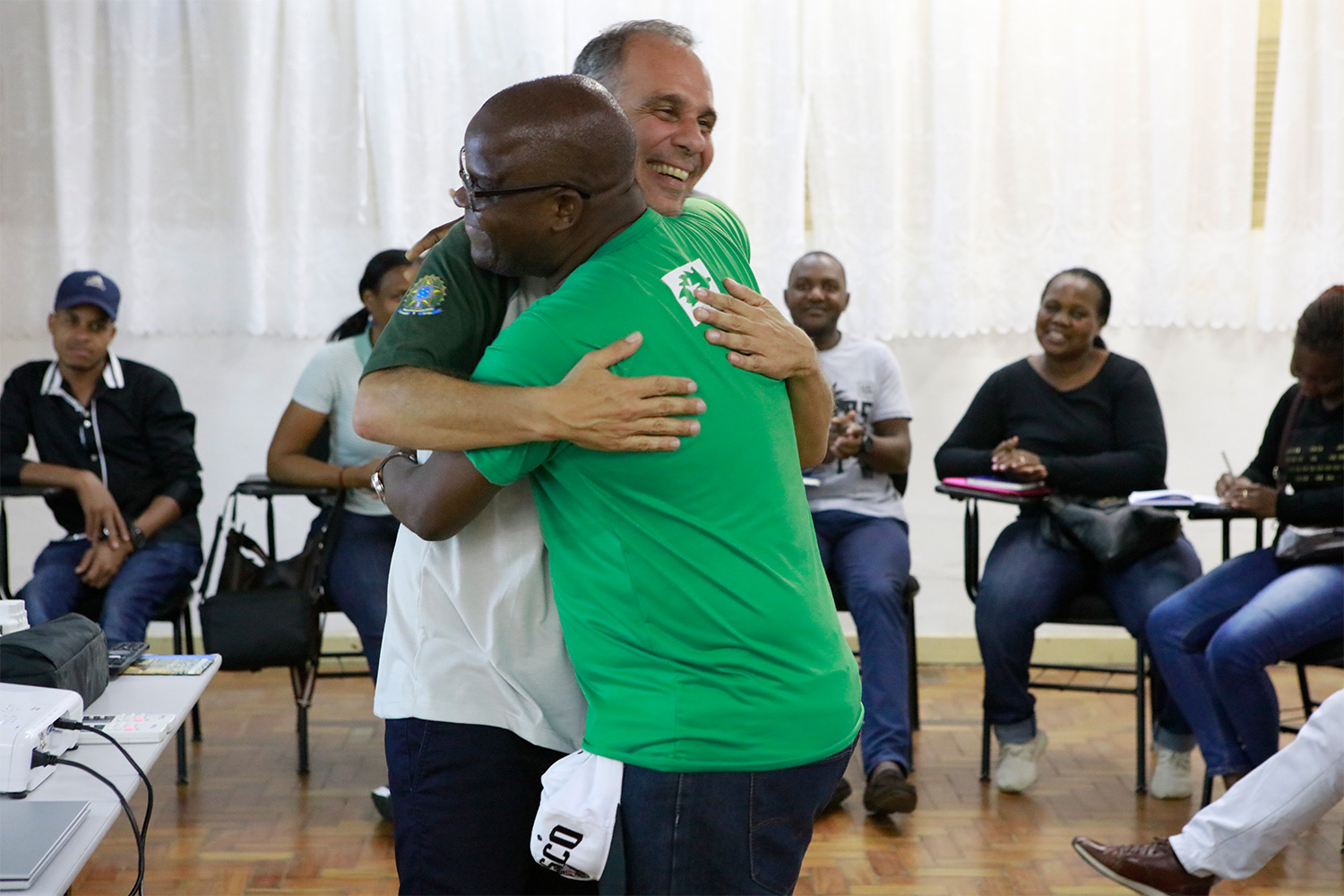 Mr. Leonardo Messias of ICMBio in Brazil and Mr. Joaquim Tembe of ADNAP in Mozambique embrace upon learning about each other's experiences in marine conservation.