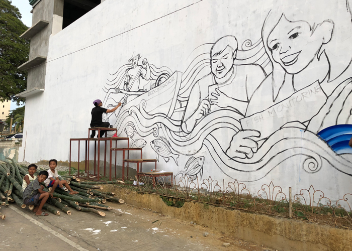 AG Sano painting a mural.