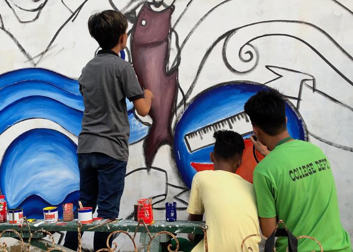 Community members painting a mural.