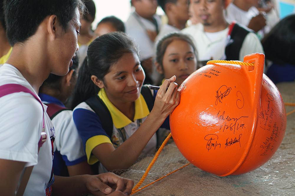 Poro student signing buoy.