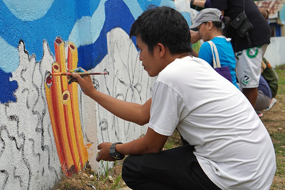 Poro art teacher painting an underwater mural.
