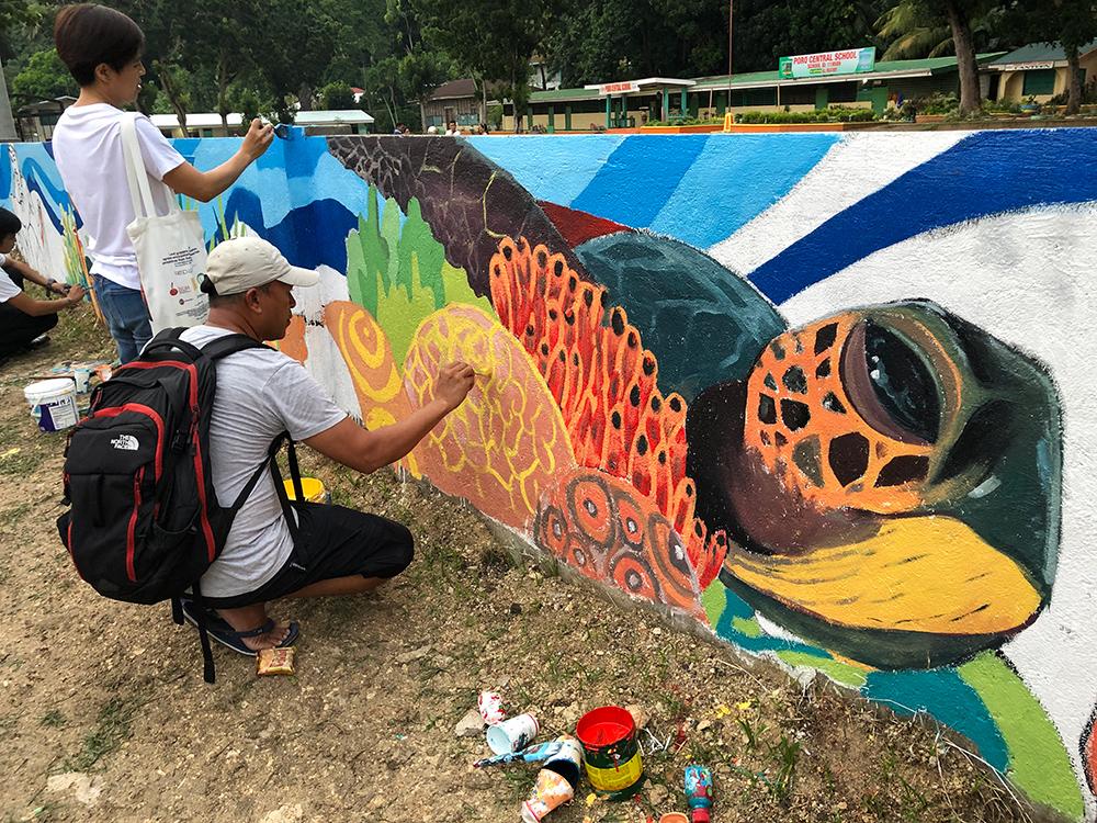 Poro man painting mural.