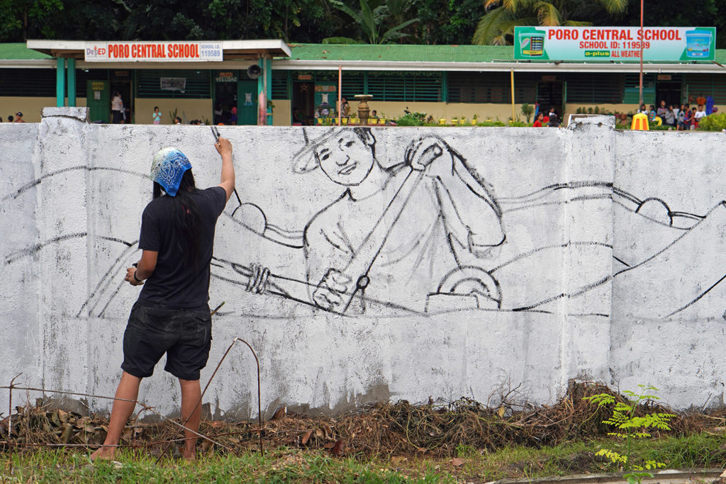 Artist AG Sano painting a mural at a school.