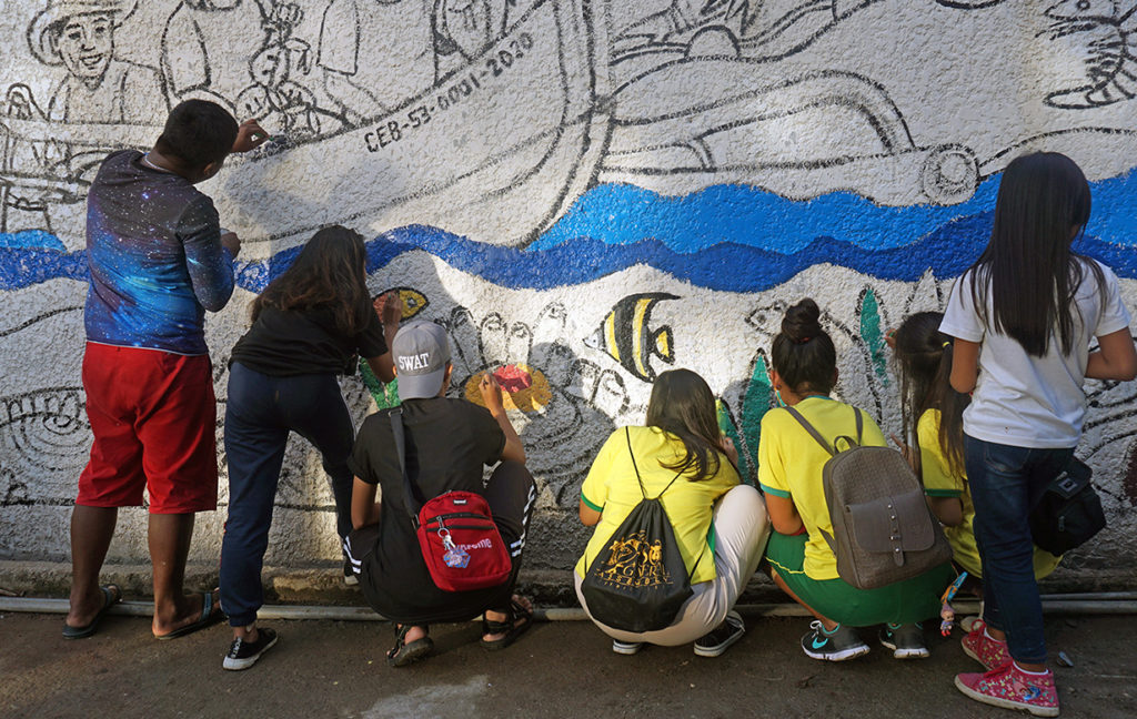 Group of youth painting a mural.