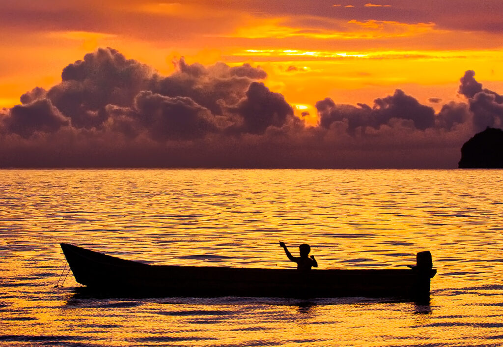 boat on the ocean at sunset.