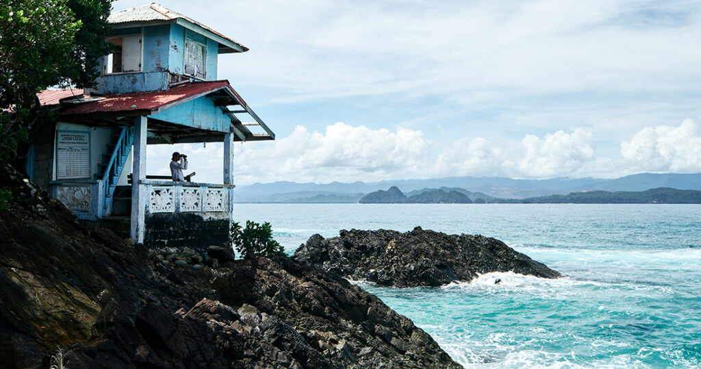 Man with binoculars looking out into the ocean in the Philippines.