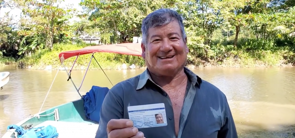 Photo of a smiling fisherman holding his new registration card.