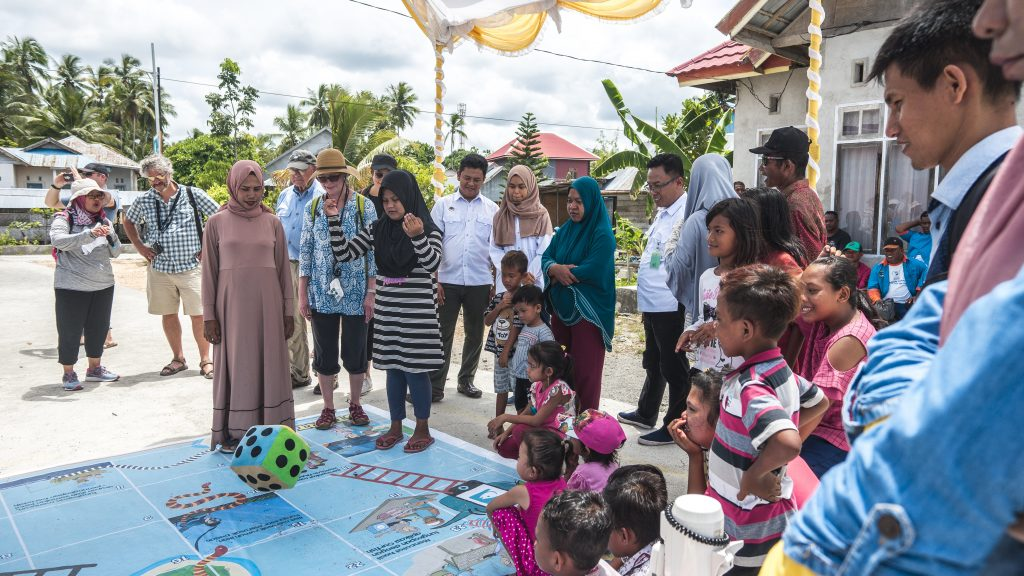 Rare Board of Trustees watching local community members play Snakes and Ladders, a game that teaches them the elements of Fish Forever in Mola, Wakatobi, Southeast Sulawesi.