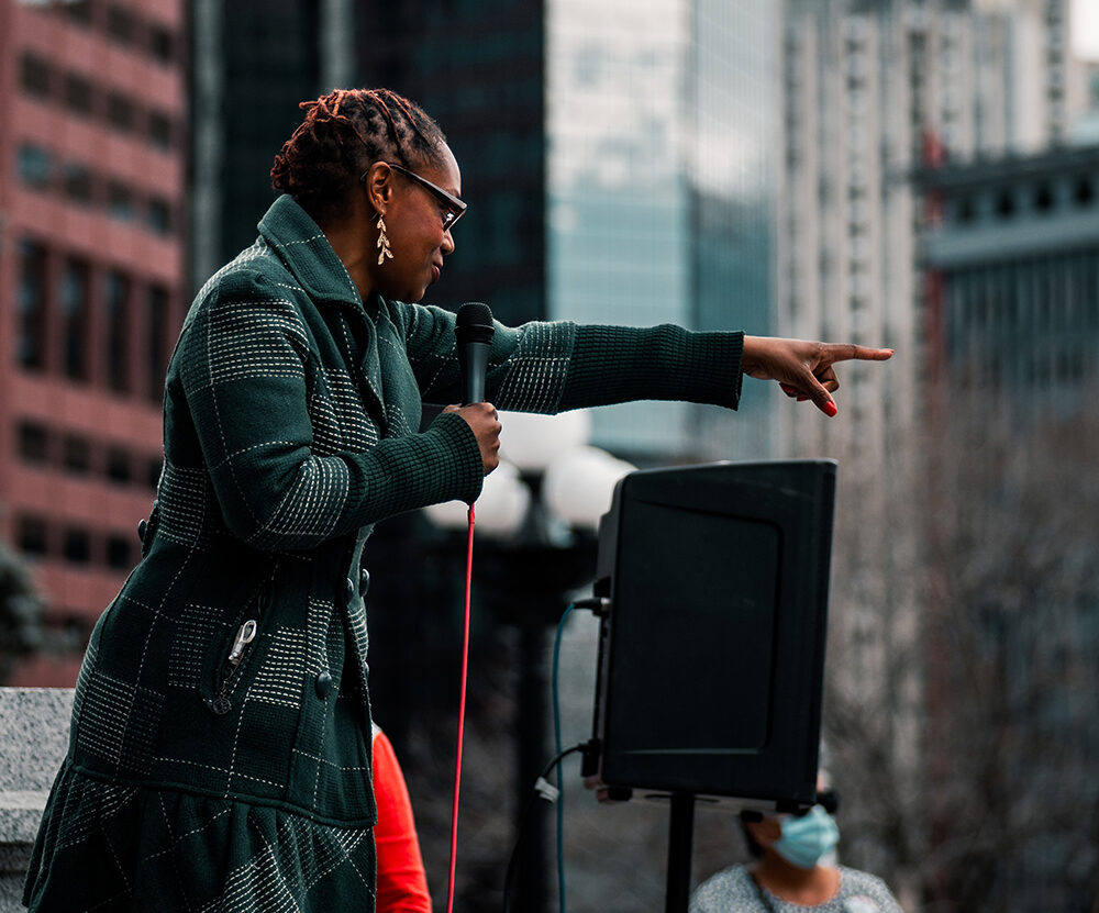 Black woman speaking at a rally in Denver, CO