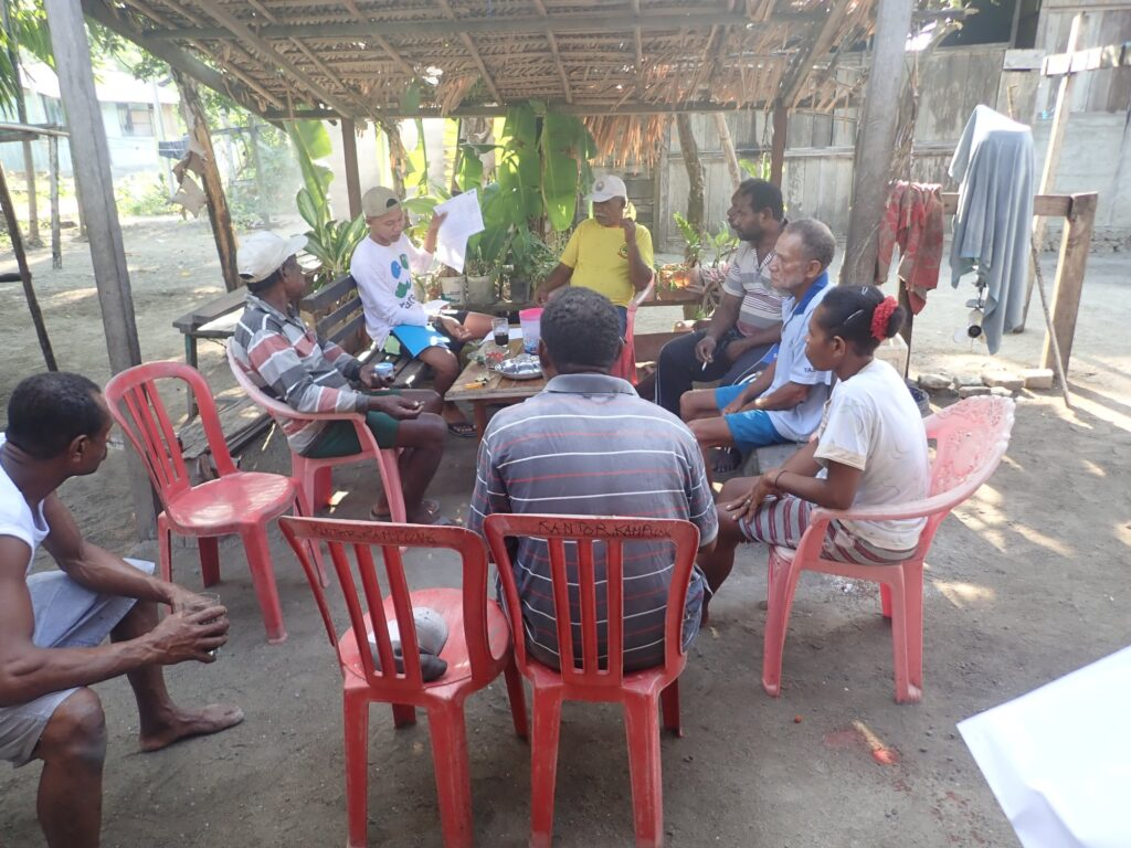 A group of people sitting around a table in Indonesia learning catch recording and reporting.